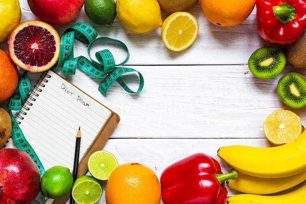 Fitnesskonzept mit obst, gemüse, maßband und lehrbuch