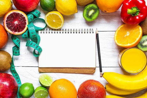 Fitnesskonzept mit obst, gemüse, orangensaft, zentimeter und lehrbuch