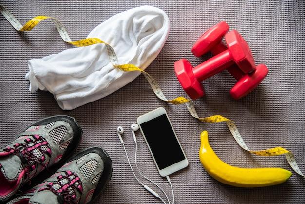 Fitnesskonzept mit übungsausrüstung auf hölzernem hintergrund.