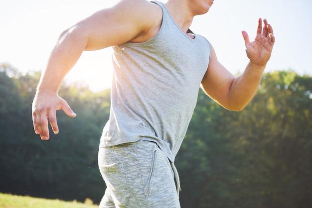 Fitnessmannathlet, der in der natur während des sonnenuntergangs joggt.