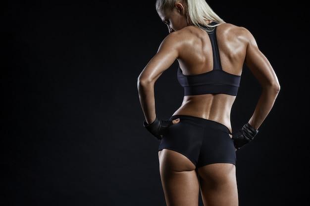Fitnessmodel posiert mit den händen auf den hüften