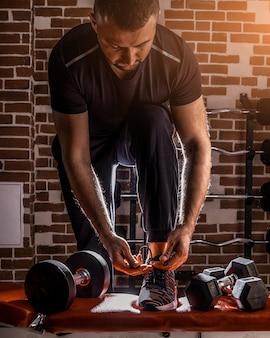 Fitnessmotivation und muskeltrainingskonzept. mann in turnschuhen, die schnürsenkel im sonnenlicht binden.