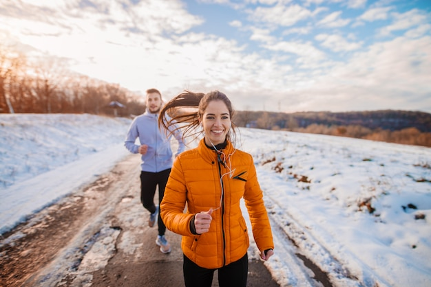 Fitnesspaar wintermorgenübung am schneebedeckten berg.