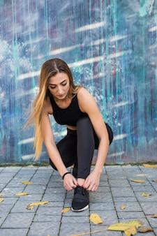 Fitnesssportfrau in modischer sportbekleidung, die yoga-fitnessübungen in der stadtstraße über grauer betonmauer macht. outdoor-sportbekleidung und schuhe im urbanen stil.