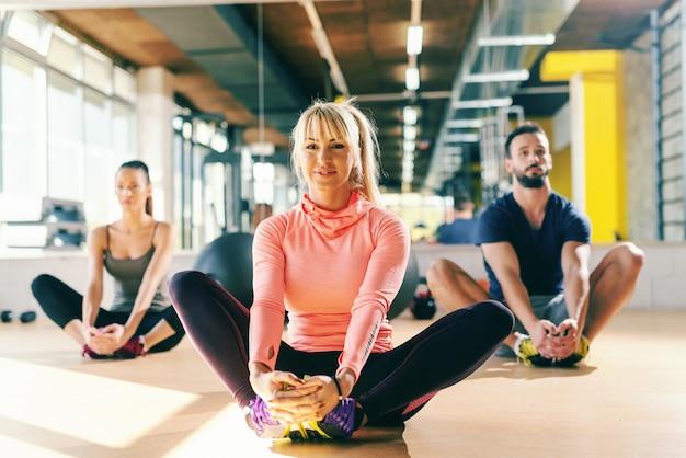 Fitnesstrainer, der sportliche paarübung für das strecken der beine beim sitzen auf dem turnhallenboden zeigt. im hintergrundspiegel.