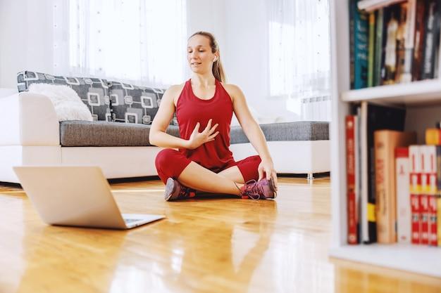 Fitnesstrainer, der zu hause auf dem boden sitzt und dem schüler die übungen erklärt
