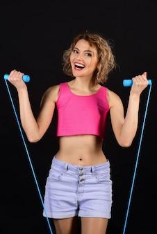 Fitnesstrainer mit springseil. lächelnder fitnesstrainer mit springseil in der hand. attraktives fitnessmädchen hält springseil. sportliches schlankes frauentraining, das ihre muskeln trainiert, um stark zu werden.