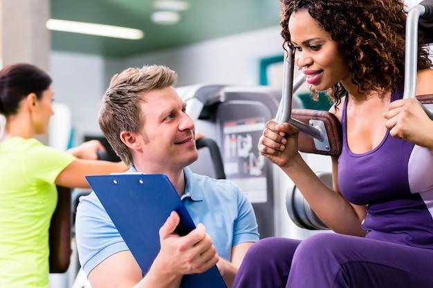 Fitnesstraining in der turnhalle - schwarze frau und persönlicher trainer