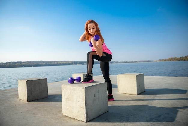 Fitnesstraining - schöne junge frau, die übung mit hanteln, als teil ihres lebensstils arbeitet.