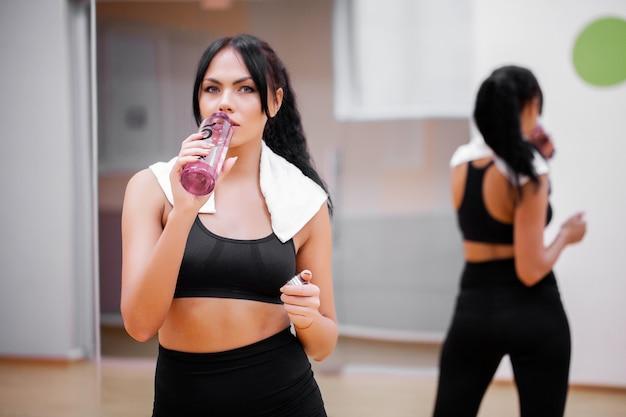 Fitnesszeit. schöne junge frau, die wasser in der turnhalle stillsteht und trinkt