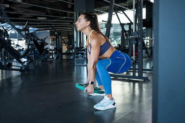 Fitte brünette macht kniebeugen mit hantelscheibe im fitnessstudio