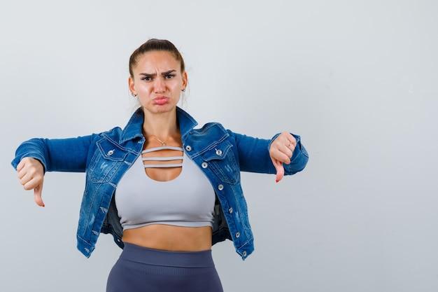Fitte frau, die doppelte daumen nach unten in bauchfreiem top, jeansjacke, leggings zeigt und verärgert aussieht, vorderansicht.