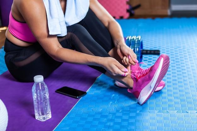 Fitte frau, die im fitnesskurs schnürsenkel an turnschuhen bindet