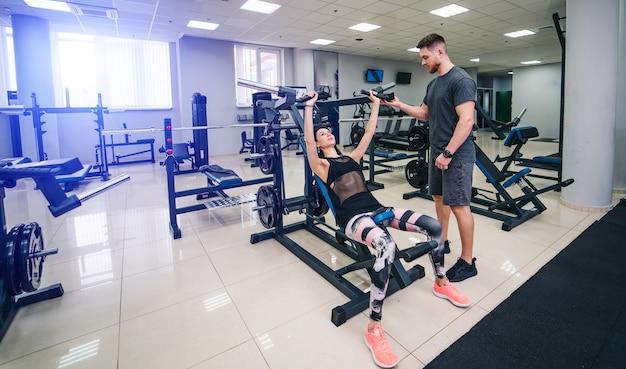 Fitte frau, die mit trainer im fitnessstudio trainiert. athlet und schönheit beim training. gesundheitsleben sportkonzept.