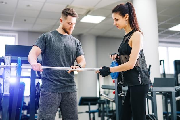 Fitte frau, die mit trainer im fitnessstudio trainiert.
