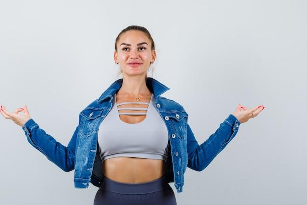 Fitte frau in bauchfreiem top, jeansjacke, leggings, die in meditierender pose steht und fröhlich aussieht, vorderansicht.