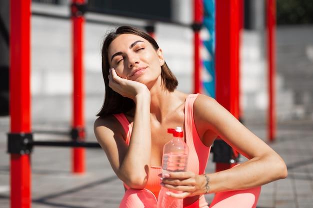 Fitte frau in rosa passender sportbekleidung im freien mit flasche wasser