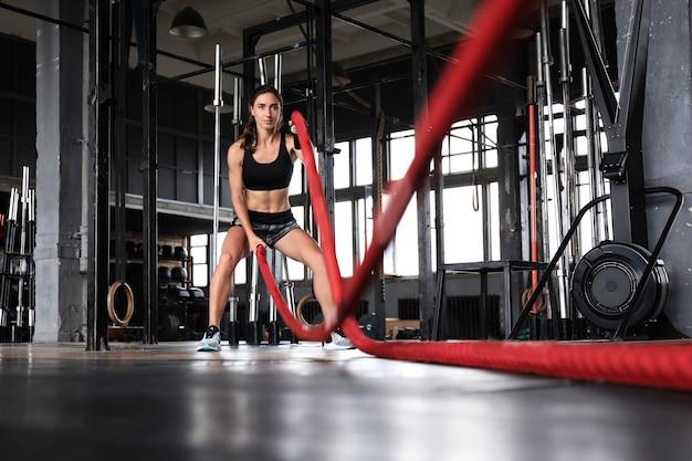 Fitte frau mit kampfseilen während des krafttrainings im fitnessstudio.