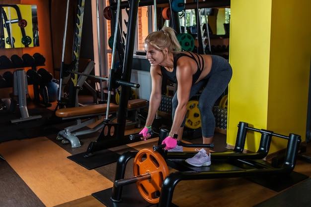 Fitte frau trainiert im fitnessstudio mit t-bar-ruder-rückentraining