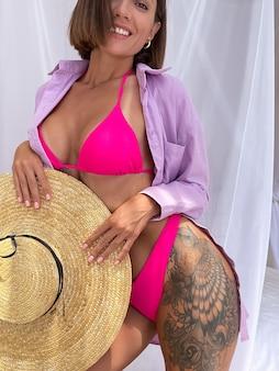 Fitte gebräunte frau mit perfektem körper im rosa sommerbikini