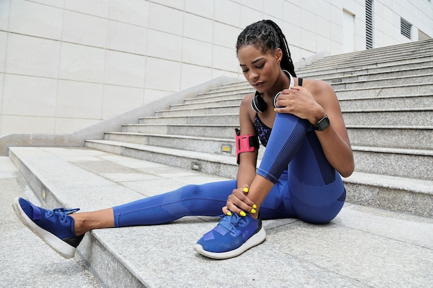 Fitte junge schwarze sportlerin, die nach dem morgendlichen joggen unter schmerzen im knöchel leidet