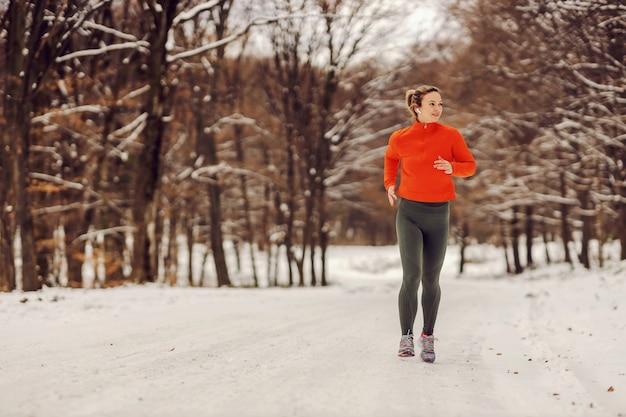Fitte sportlerin, die an einem verschneiten wintertag in der natur läuft. kaltes wetter, schnee, gesundes leben, fitness, gesunde gewohnheiten