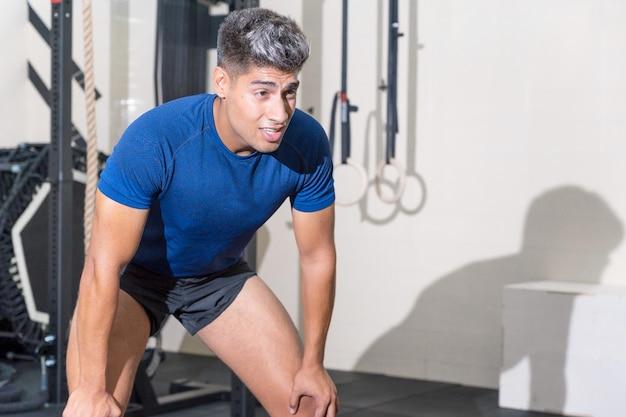 Fitter junger mann, der nach einer trainingseinheit im fitnessstudio schwitzt