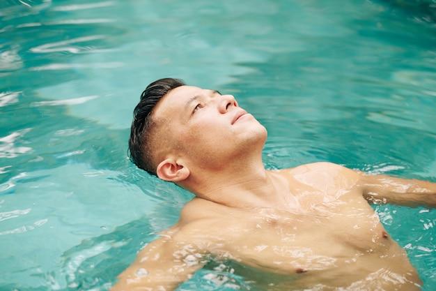 Fitter mann, der auf dem rücken im schwimmbad schwimmt und in den himmel schaut