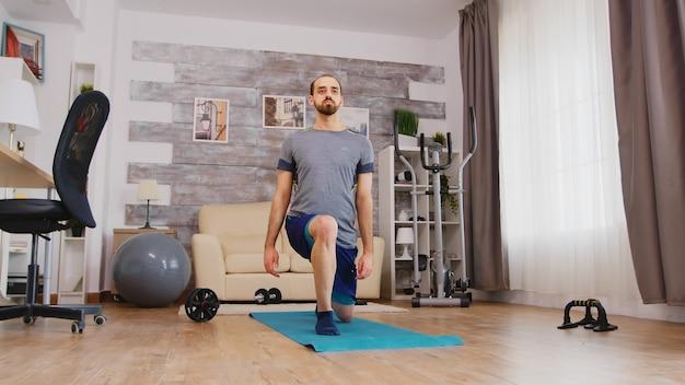 Fitter mann trainiert seine beine zu hause auf der yogamatte nach vorne.