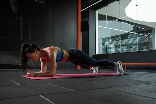 Fittes mädchen, das die vordere ellbogenplanke auf der matte im fitnessstudio macht