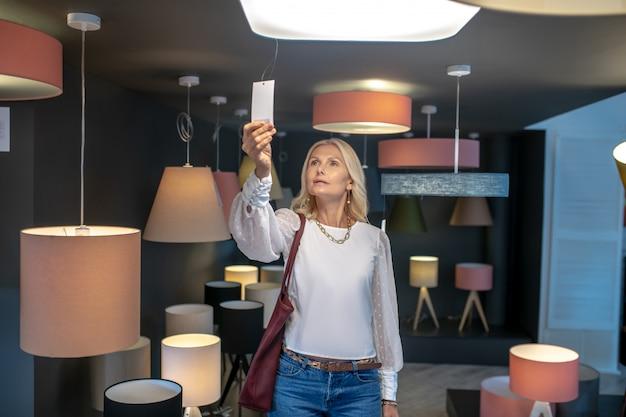 Fixtures, eine wahl. frau in der beleuchtungsabteilung eines möbelhauses, das das preisschild der pendelleuchte betrachtet, ist ernst.