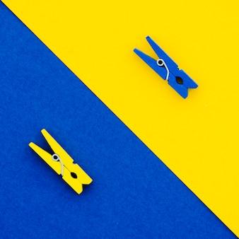 Flach gelegte blaue und gelbe wäscheklammern