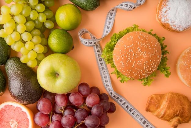 Flach gelegte früchte und ungesunde lebensmittel mit maßband