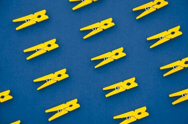 Flach gelegte gelbe kleidungsstifte vom blauen hintergrund