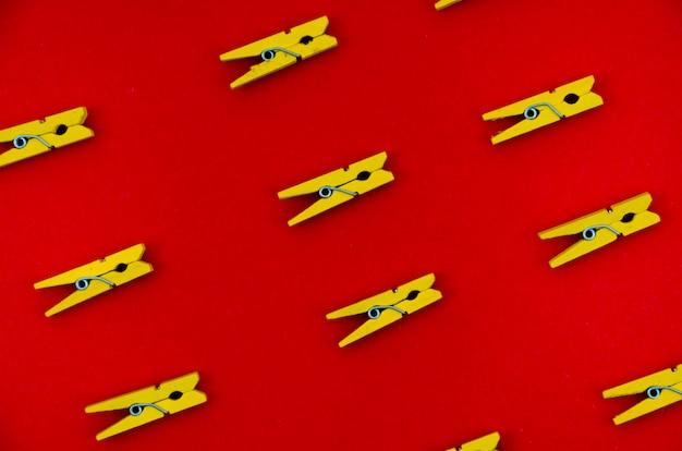 Flach gelegte gelbe kleidungsstifte vom roten hintergrund