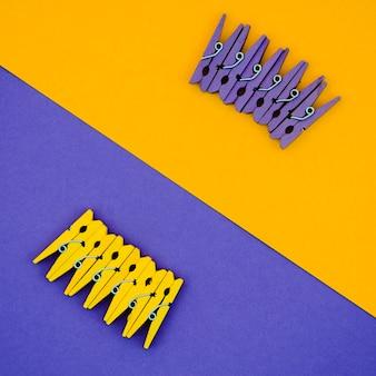 Flach gelegte gelbe und lila wäscheklammern