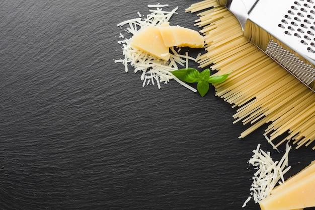 Flach gelegte geriebene parmesanreibe und ungekochte spaghetti mit kopienraum