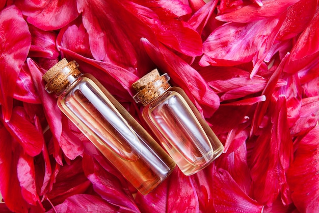 Flach gelegte glasflaschen mit essenz aus blütenblättern