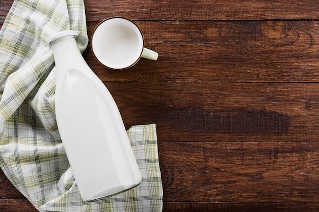 Flach gelegte milchflasche mit tasse
