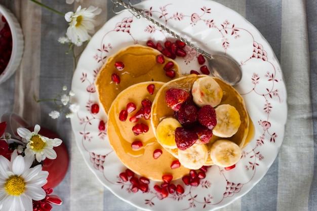 Flach gelegte pfannkuchen mit granatapfelkernen, bananen und himbeeren