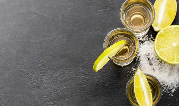 Flach gelegte tequila-aufnahmen und limettenscheiben mit kopierraum