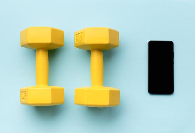 Flach gelegtes draufsicht-smartphone mit sportgeräten auf blauer oberfläche