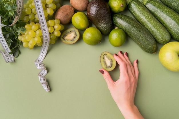 Flach gelegtes obst und gemüse mit hand, die kiwi hält