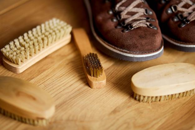 Flach gelegtes schuhwerk mit draufsicht und schuhzubehör aus wildlederschuhen, bürste auf holztisch.
