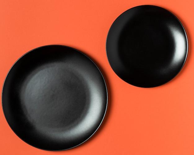 Flach gelegtes schwarzes tellersortiment