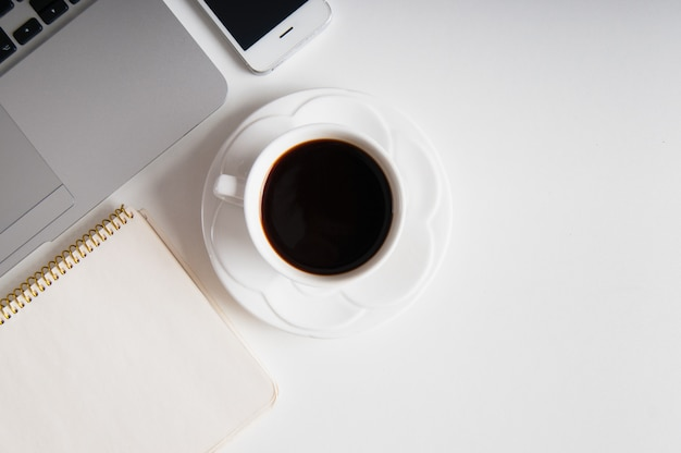 Flach lag auf weißem holzarbeitsplatz mit laptop, handy-gerät und schwarzem kaffee.