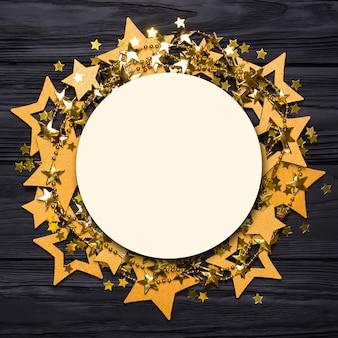Flach lag ein leerer runder rahmen aus großen und kleinen konfetti-sternen. goldene perlen in form von sternen.