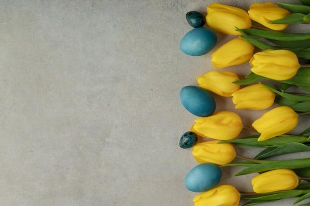 Flach lag mit blauen natürlich gefärbten ostereiern und gelben blumen auf grauem tisch
