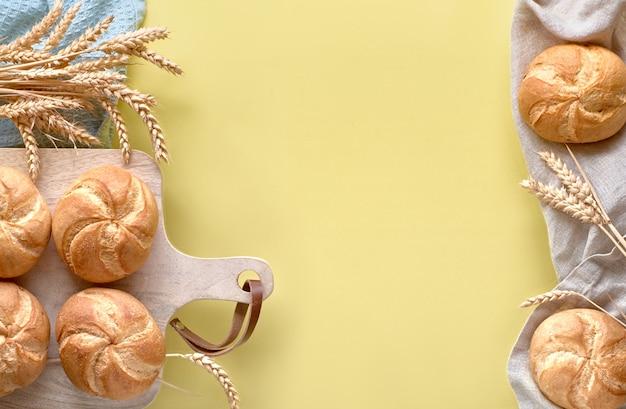 Flach lag mit brötchen, bekannt als kaiser- oder wiener brötchen, auf gelbem papierhintergrund