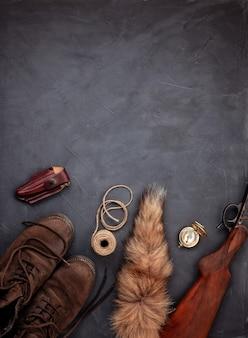 Flach lag mit jagdmunition über dem grauen hintergrund: alte stiefel, gewehr, messer, seil, gürtel, fuchsschwanz.
